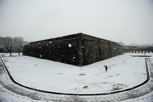 A woman goes for a walk with a dog as the snow falls covering the city in Pamplona, Spain