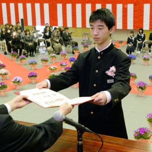 A graduating student of the Okuma Junior High School, which used to be 4km from the crippled Fukushima Daiichi nuclear power plant, receives his graduation certificate during a ceremony at the temporary buildings.