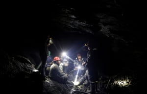 Artisanal gold miners talk as they sit inside a mine in La Rinconada
