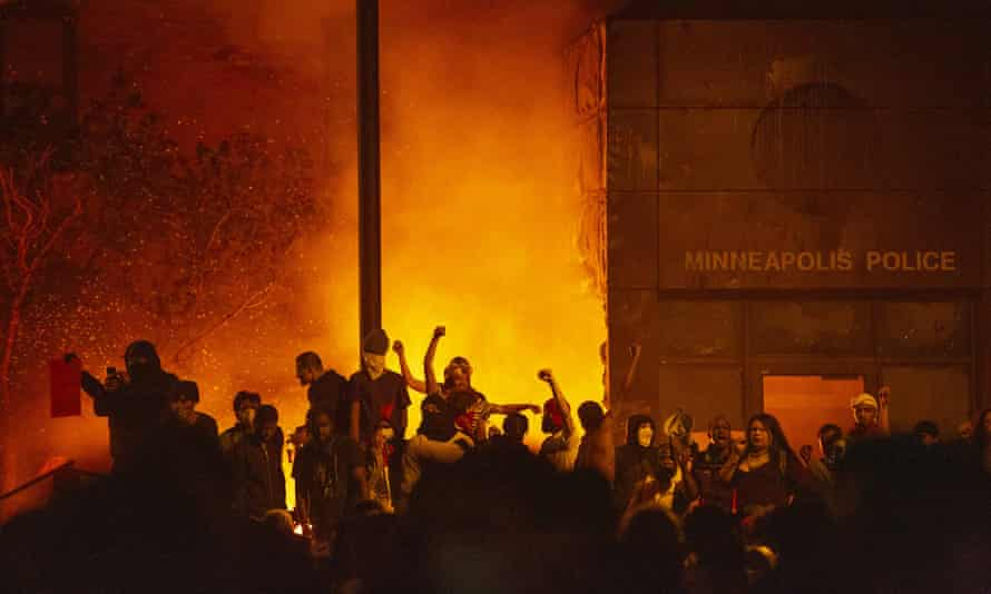 Protesters raise their fists as the 3rd police precinct burns in Minneapolis, Minnesota.