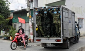 Vietnamese soldiers look out from a truck as they deliver food in strict lockdown areas in Ho Chi Minh