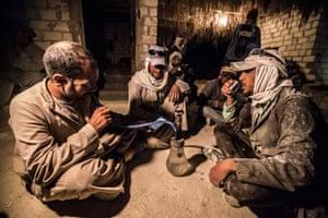 Men sat cross-legged smoking water pipe