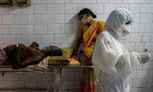 A woman leans against a stretcher holding her husband in the corridor of the emergency ward of a hospital in Bhagalpur, in the eastern state of Bihar.