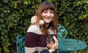 Donna, grinning, sitting at a garden table with a rat on her shoulder and another in her hands