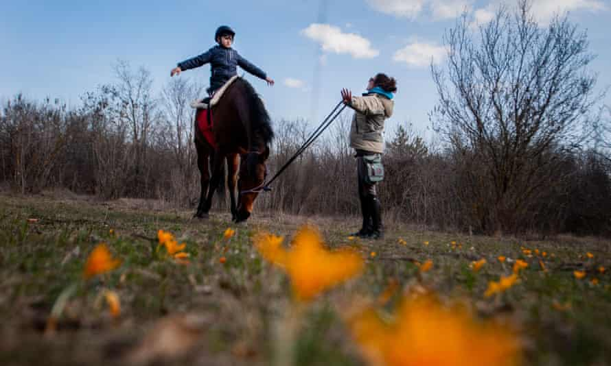 A boy sits on a horse while his therapist stands nearby