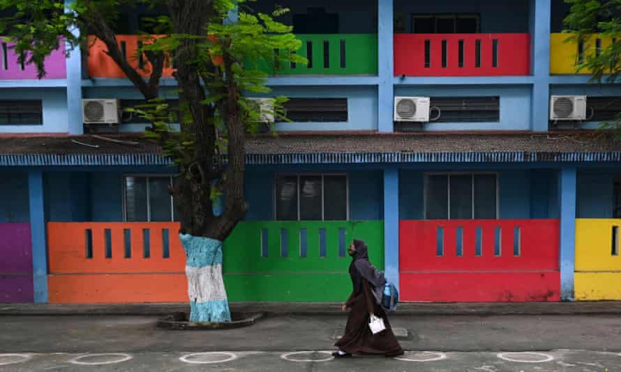 A student arrives to attend classes at a school at a school in Chennai after the state government relaxed restrictions for schools