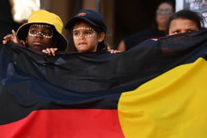 Children hold an Aboriginal flag outside Sydney Town Hall