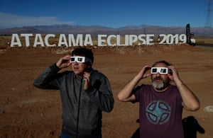 Tourists try special glasses to watch an eclipse at the entrance of an astronomical camp in the commune of Vallenar in the Atacama desert about 600km north of Santiago.