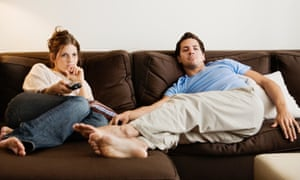 Young couple on a sofa watching TV, the woman looking bored