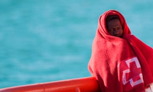 A migrant wrapped in a Red Cross blanket