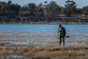 Just 30 minutes after the opening of hunting season, with virtually no ducks now around to shoot, a hunter checks his mobile phone whilst standing in Little Lake Buloke. In April the 2021 bag limit for shooters was increased from two to five birds a day, angering conservationists