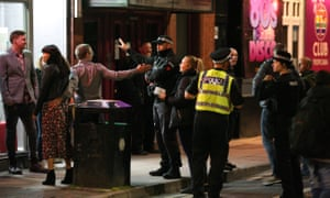 Police talk to people in Manchester on the first Saturday night since the introduction of the 10pm curfew