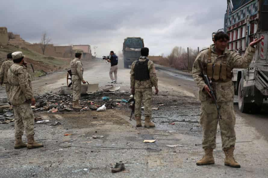 2013: Afghanistan security forces stand guard after a roadside bomb exploded under an Afghan bus, killing nine in an attack blamed on Taliban militants.