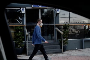 A man wearing in a mask is seen through a car window as he walks outside of a closed pub in central Nicosia, Cyprus