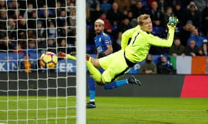 Leicester City's Riyad Mahrez watches as his shot curls round the Huddersfield Town goalkeeper Jonas Lössl to open the scoring.