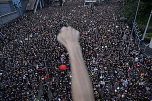 A protester clenches his fist as tens of thousands march through Hong Kong in opposition to an unpopular extradition bill.