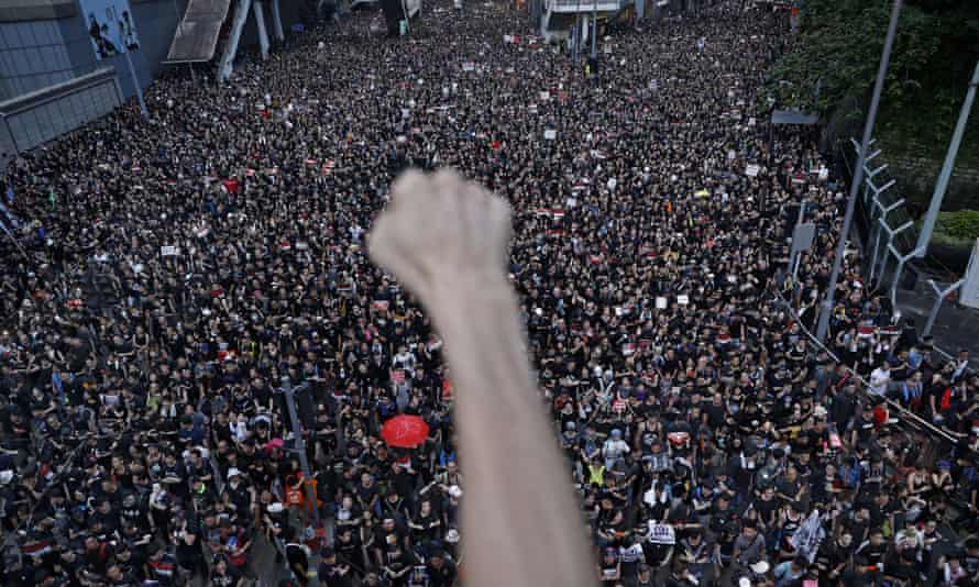 A protester clenches their fist as tens of thousands of protesters march on the streets of Hong Kong.