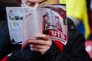 A fan reads the match programme.