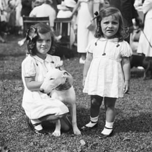 Jacqueline, aged six, and Lee Bouvier play with their dog Regent, a bull terrier, at a dog show in East Hampton, Long Island in 1935