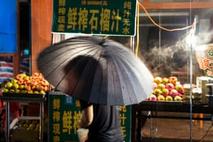 Xi'an, north-west China, and a women holding clear umbrella walks past a grocer's store where fruit and vegetables are arranged outside it.  As the eastern departure point of the Silk Road, the ancient imperial capital became a hub of diverse ethnic identities and religious beliefs. Next to the city's Great Mosque are the bustling lanes of the Muslim quarter