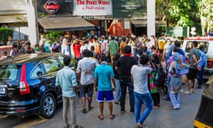 People are seen gathering outside a liquor shop in Mumbai, India on 4 May 2020.