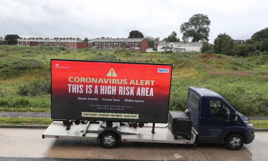 A mobile advertising vehicle displaying a coronavirus high risk area warning in Oldham, Greater Manchester
