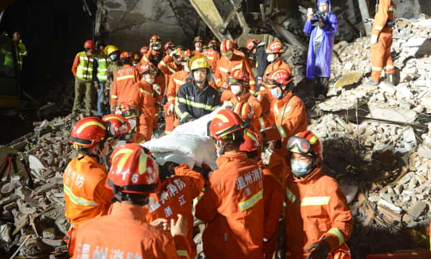 Rescuers transfer a girl at the site where residential buildings collapsed in Lucheng industrial district in Wenzhou city.