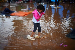 Rosa Julia Romero, a four-year-old migrant girl from Honduras, part of a caravan of thousands from Central America trying to reach the United States, wears her mother's shoes as she walks through a temporary shelter after heavy rainfall in Tijuana, Mexico, November 29