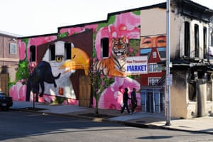 A Korean owned shop burned out during the violence after the death of Freddie Gray is painted with Black Power symbols and a portrait of the shop's owner by the street artist Gaia