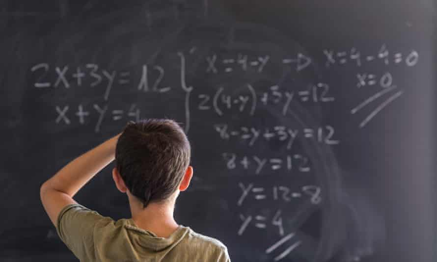Child at blackboard with maths problem.