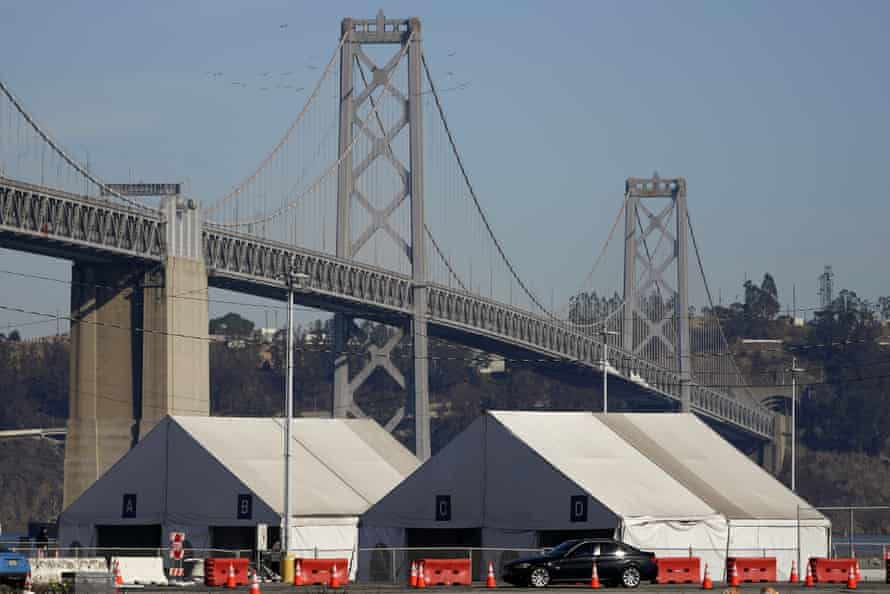 Tents from a Covid testing site in San Francisco sit in front of the San Francisco-Oakland Bay bridge.