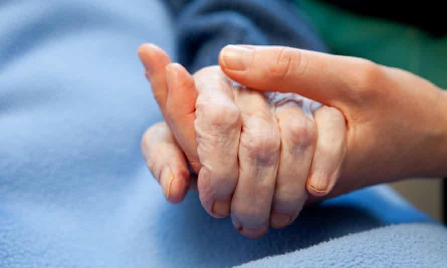 A carer holding the hand of an elderly person
