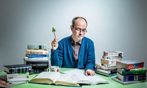 Quiz setter Thomas Eaton sitting at a desk piled with books