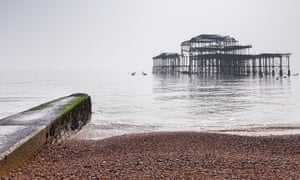 Brighton Beach and the remains of the old West Pier on a foggy day in flat light, Sussex, England.
