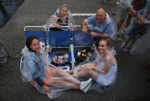 A family take shelter from their Cahill Expressway vantage point on Sydney Harbour