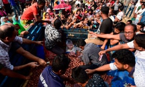 People scuffle as they purchase subsidised onions in Dhaka on Sunday.