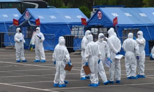 Government workers in protective clothing outside a tent used to coordinate transporting people from Wuhan to quarantine in Beijing.