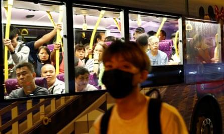 Bus passengers watch a protester walking along the main road from Hong Kong international airport.