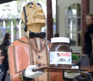 wooden statue of a waiter carrying a tray with a giant jar of Nutella