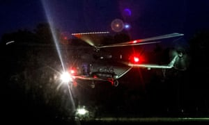 A helicopter lands at a military airport in Chiang Rai. Its passengers are then taken by ambulance to nearby hospital.