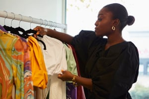 Fisayo Longe hanging clothes on a rail
