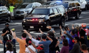 People react as the motorcade carrying US President Donald Trump returns to the White House on November 7, 2020.