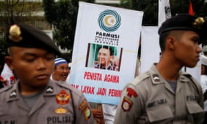 A Muslim protester holds a banner during a rally outside a court during a controversial blasphemy case against Jakarta's Christian governor.