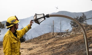 Yucaipa, US Fire engineer, Paul Kahler, examines a melted light post destroyed by the El Dorado wildfire in California