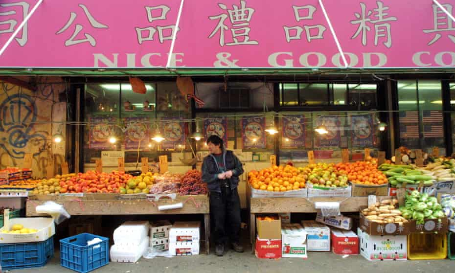 A vendor stands at an empty fruit and vegetable stand in Chinatown, New York City, in November 2001.