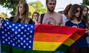 People commemorate the victims of the mass shooting at a gay nightclub in Orlando at the US embassy in Warsaw on Monday