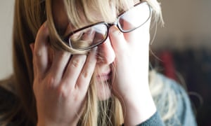 A woman rubbing her eyes under her glasses, and looking frankly shattered