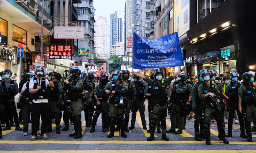 Hong Kong riot police hold up warming sign during an unauthorized rally on September 6