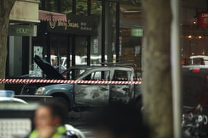 A burnt out vehicle is seen in Bourke St.