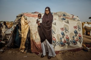 A woman and her child pose outside of their makeshift home built from a collection of fabrics inside the Farm Centre IDPs camp in Maiduguri, Nigeria.